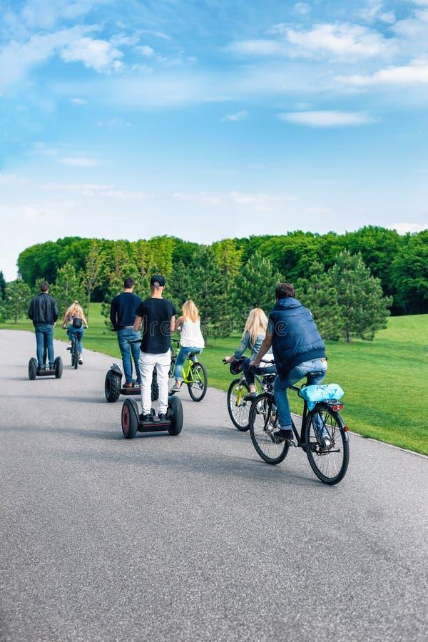Езда велосипедистов вдоль пути велосипеда в парке стоковые фото