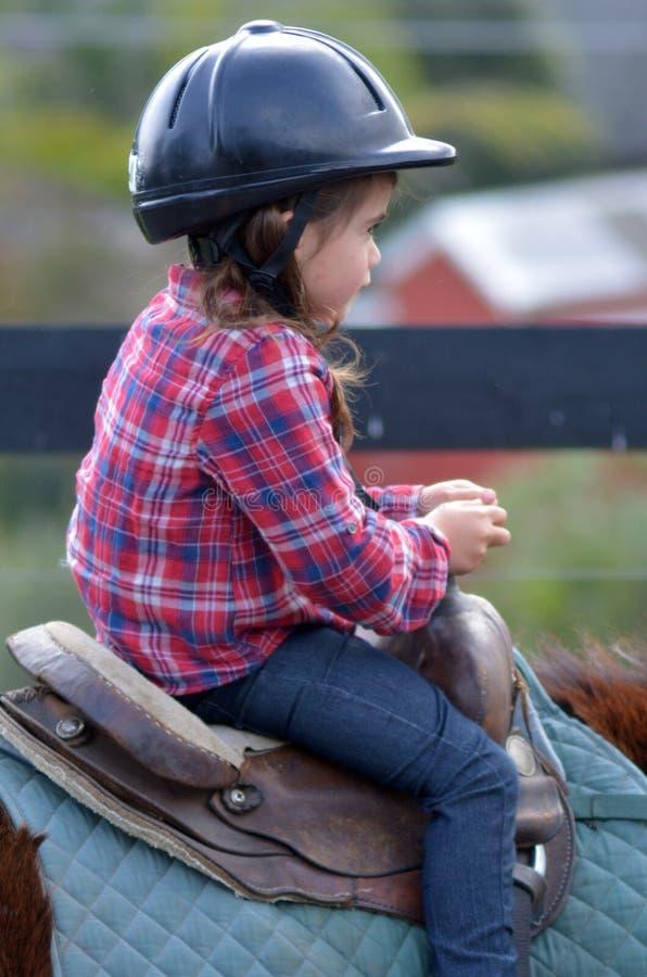 Езда маленькой девочки лошадь во время урока лошади освобождая стоковое фото