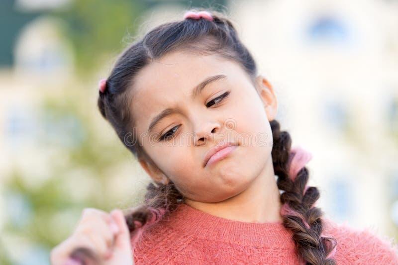 Ей нужен хороший парикмахер Милая маленькая девочка смотря длинные заплетенные волосы Парикмахер детей Салон парикмахера для стоковая фотография rf