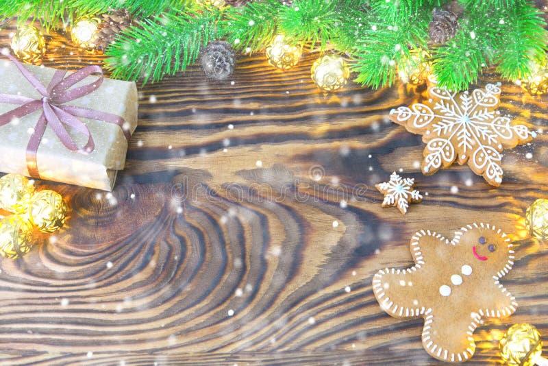 Ель рождества с домодельными печеньями, подарком и светами пряника на старой деревянной предпосылке с космосом рождество веселое стоковое фото rf