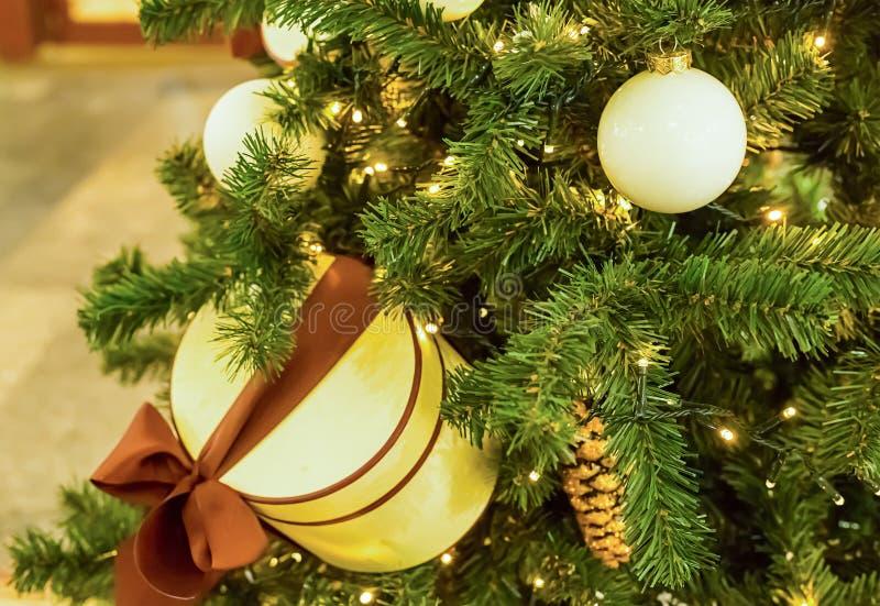 Ель украшенная с накаляя гирляндой с электрическими лампочками, белым сияющим шариком рождества и круглой cream коробкой стоковое фото