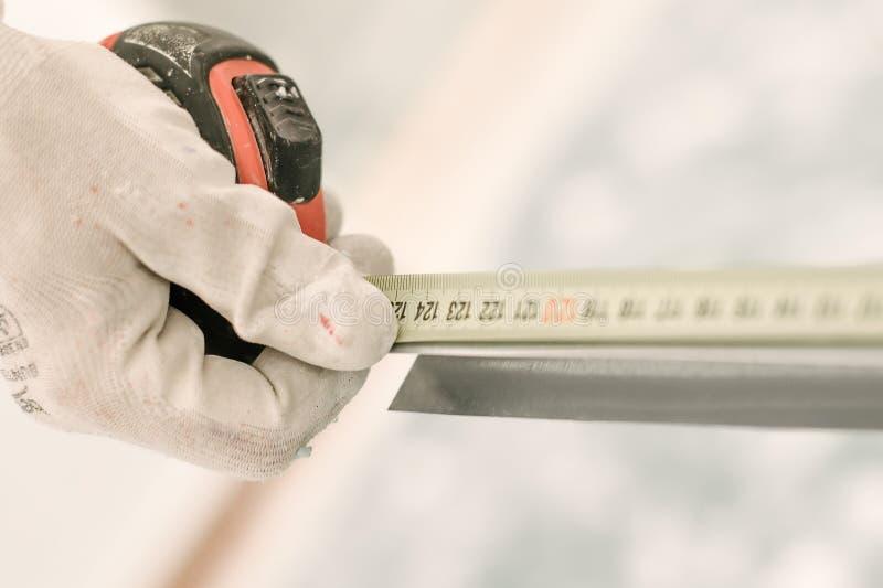 лента конструкции измеряя используя работника стоковая фотография rf