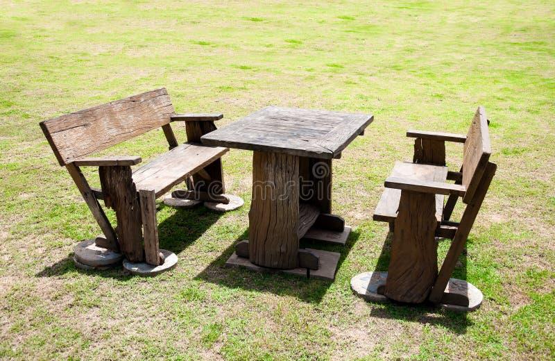 деревянный стол и стул на времени двора зеленой травы в полдень стоковое изображение