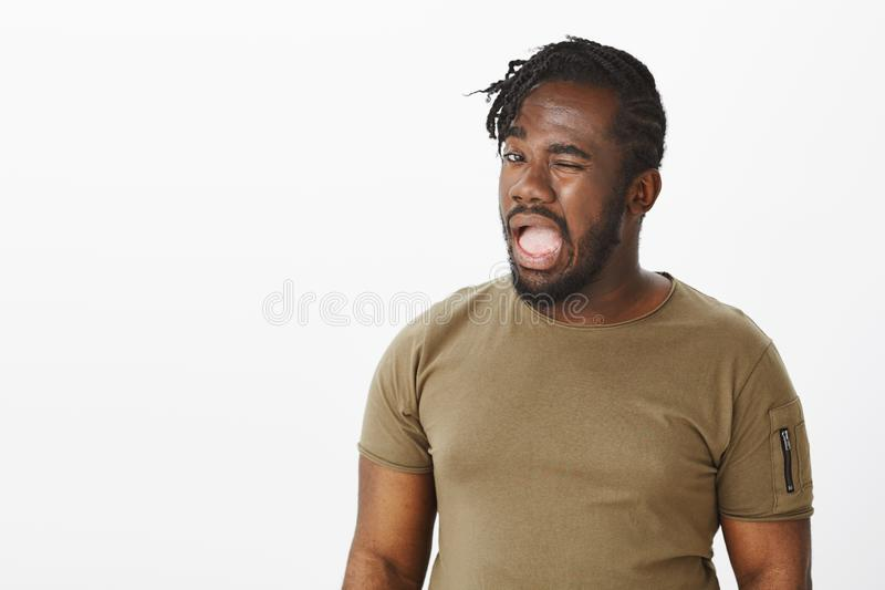 Если вы знаете, то чего я значу Портрет интриговать смешной Афроамериканца в вскользь футболке, подмигивая с раскрытым ртом стоковое фото rf