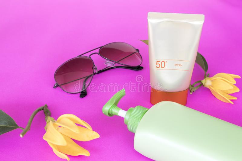 Естественная косметика sunsceen spf50 с цветком ylang на пинке стоковое изображение rf