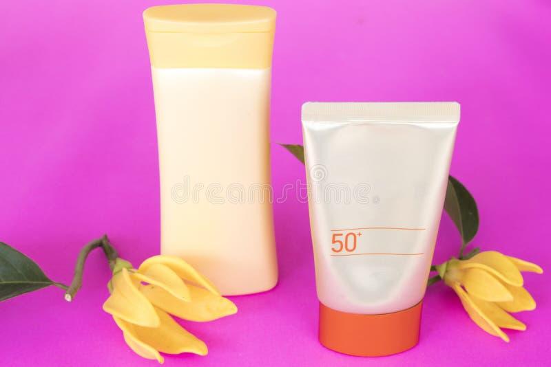 Естественная косметика sunsceen spf50 с цветком ylang на пинке стоковая фотография rf