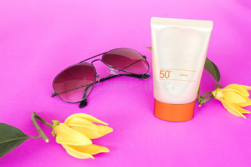 Естественная косметика sunsceen spf50 с цветком ylang на пинке стоковые фотографии rf