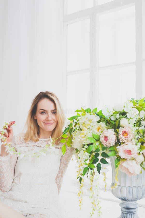 Естественная молодая женщина представляя с цветками стоковое фото rf