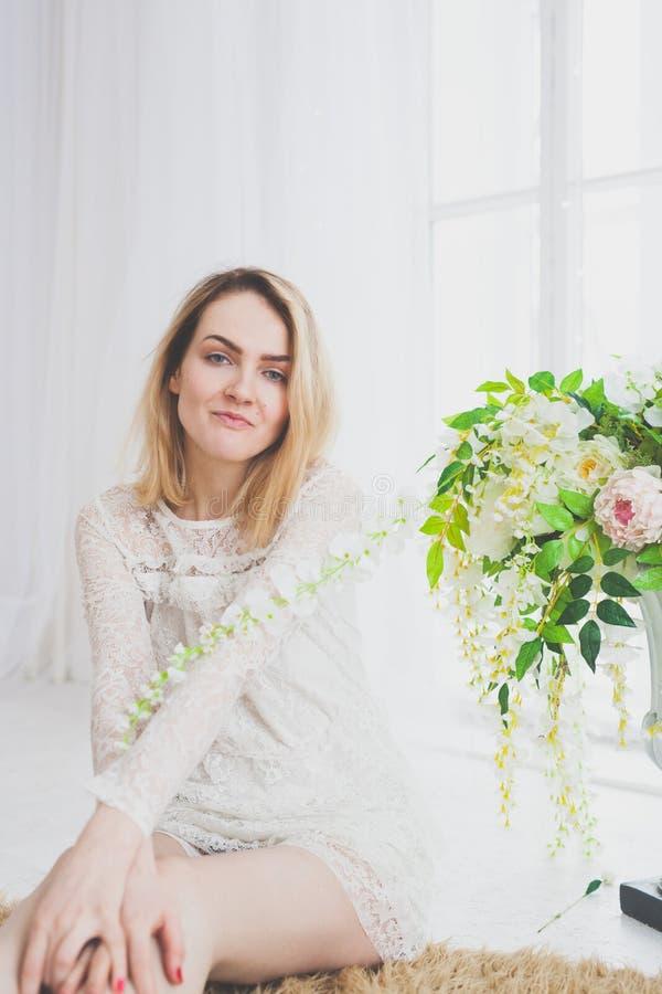 Естественная молодая женщина представляя с цветками стоковая фотография rf