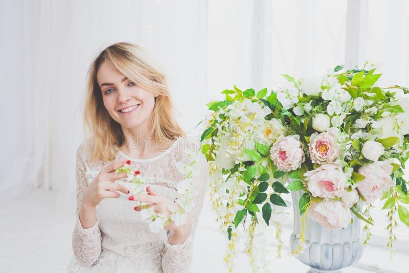 Естественная молодая женщина представляя с цветками стоковое изображение rf