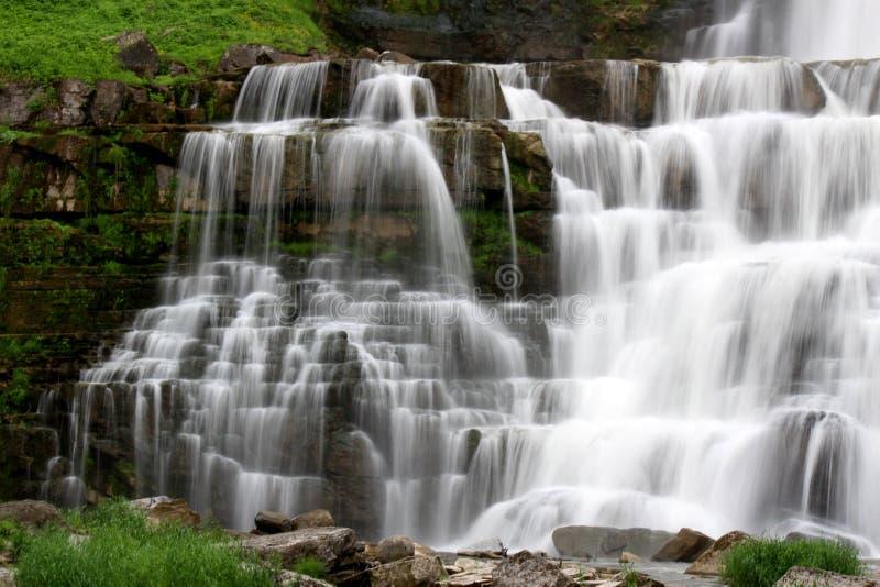 Естественная обстановка водопадов каскадируя над несколькими слоев утеса и седимента к тазу ниже стоковое изображение