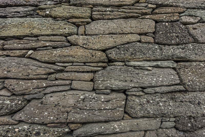 Естественная предпосылка каменной стены с скачками камнями в тенях серого цвета с малыми черно-белыми пятнами - детали старых руи стоковые фотографии rf