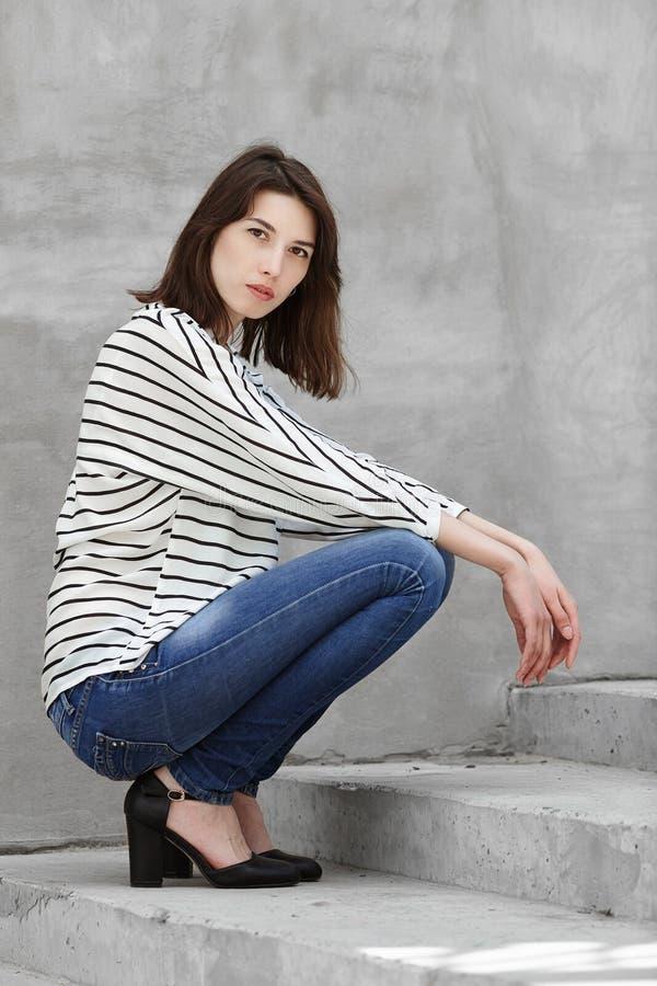 Естественного света портрет outdoors модели молодой модной женщины брюнет практикуя представляя outdoors против городского backgr стоковая фотография rf