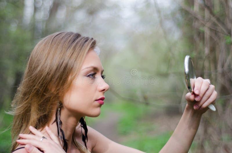 Естественно красивая молодая белокурая женщина в природе держа зеркало стоковые изображения