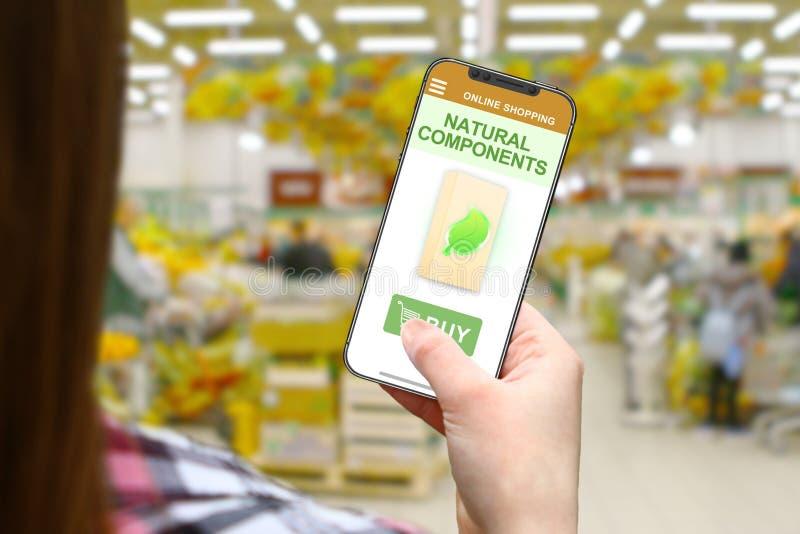 Естественные компоненты идея, девушка с frameless телефоном на запачканной предпосылке магазина стоковая фотография rf