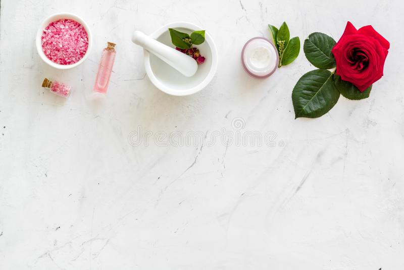 Естественные флористические косметики с розовыми цветками для заботы стороны и тела на белой мраморной насмешке взгляда сверху пр стоковые фото
