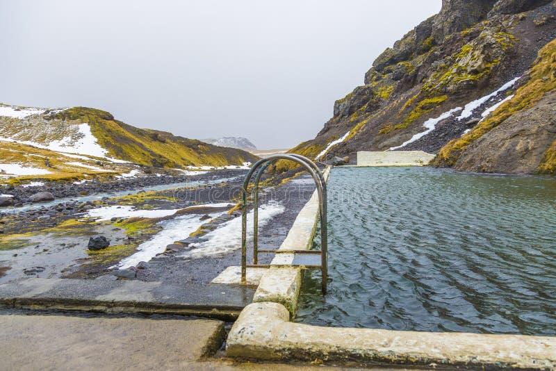 Естественный бассейн Seljavallalaug в Исландии с человеком в воде и снежных погоде и горах совсем вокруг стоковая фотография rf