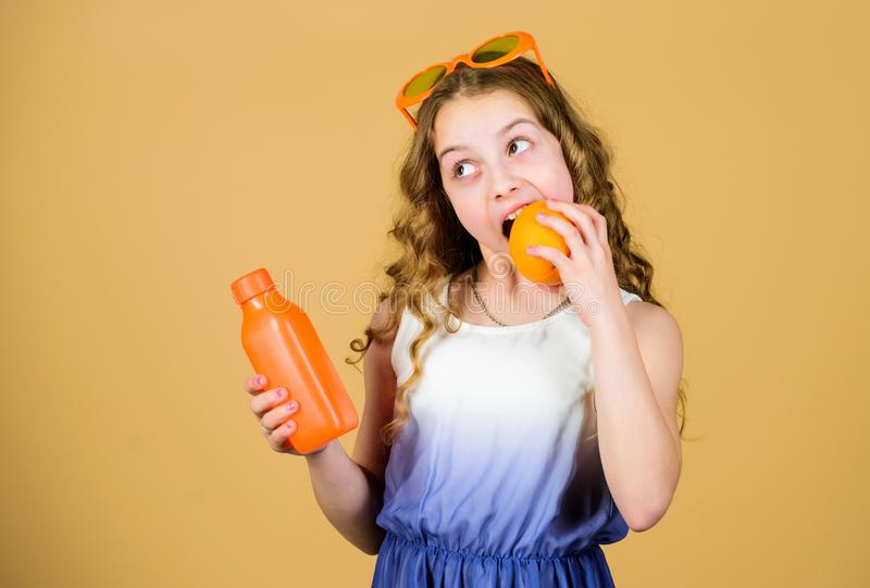 Естественный источник витамина Девушка ребенк ест оранжевый плод и выпивает апельсиновый сок Питание витамина Солнечные очки ребе стоковое изображение