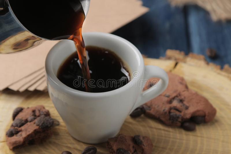 Естественный кофе эспрессо полит с Cezve в чашку на голубом деревянном столе стоковые изображения rf