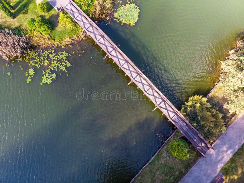 Естественный ландшафт, воздушный взгляд сверху деревянный старый footbridge над большим озером воды стоковое изображение