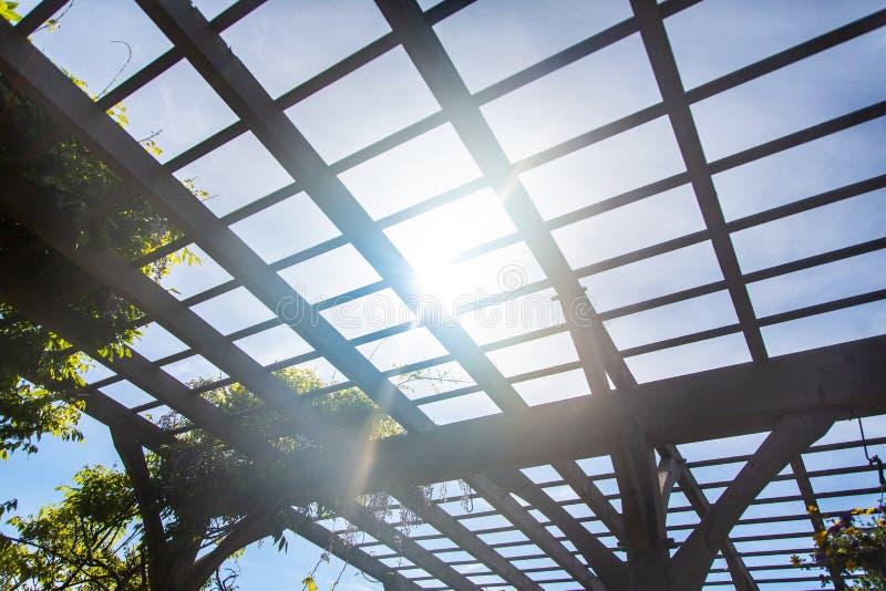 Естественный показ солнечного света через деревянную сень беседки стоковое фото