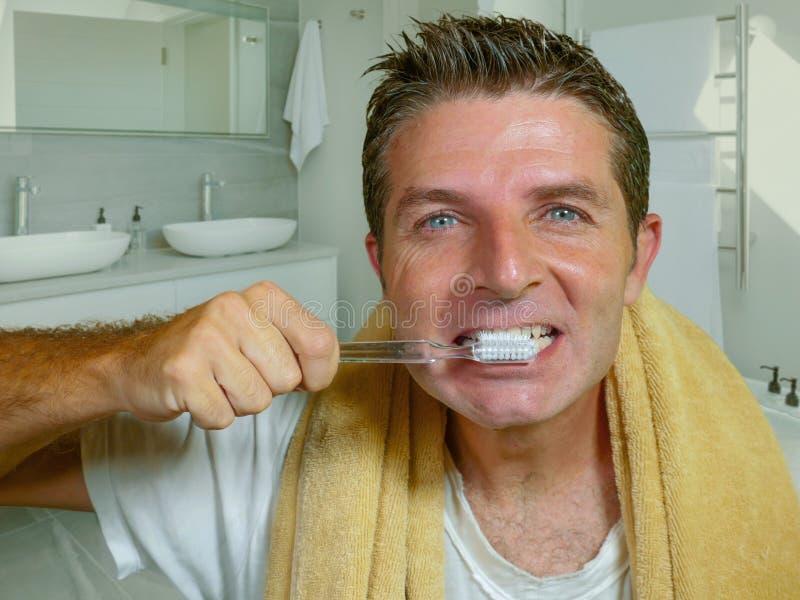 Естественный портрет образа жизни молодого привлекательного и счастливого кавказского bathroom человека дома моя его зуб со смотр стоковые фотографии rf