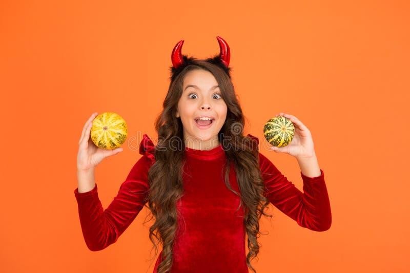 Есть тайна Хэллоуина Счастливого ребенка с загадочным взглядом Маленькая девочка в рогах красного дьявола держит тыквы Добавить т стоковые фотографии rf