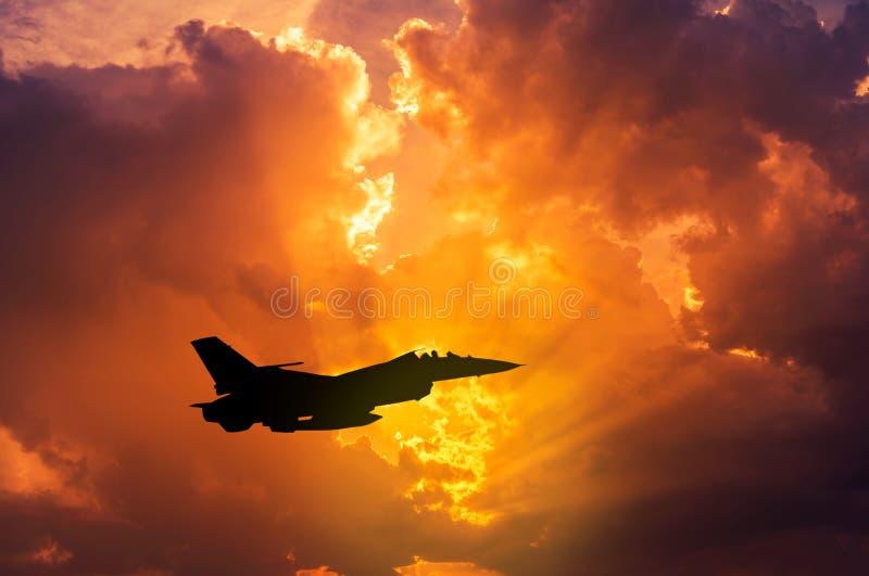 летание военного самолета реактивного истребителя сокола силуэта на заходе солнца стоковое фото rf