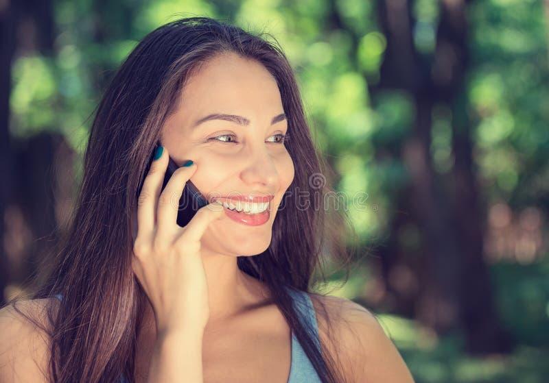 детеныши женщины красивейшего мобильного телефона говоря стоковая фотография