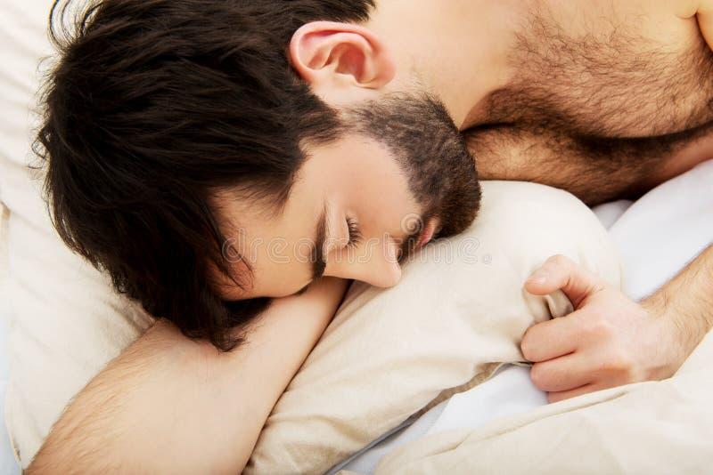 детеныши спать человека кровати стоковое изображение