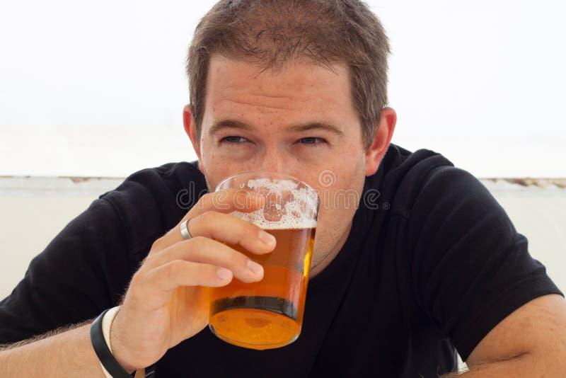 детеныши человека пива выпивая стоковое фото