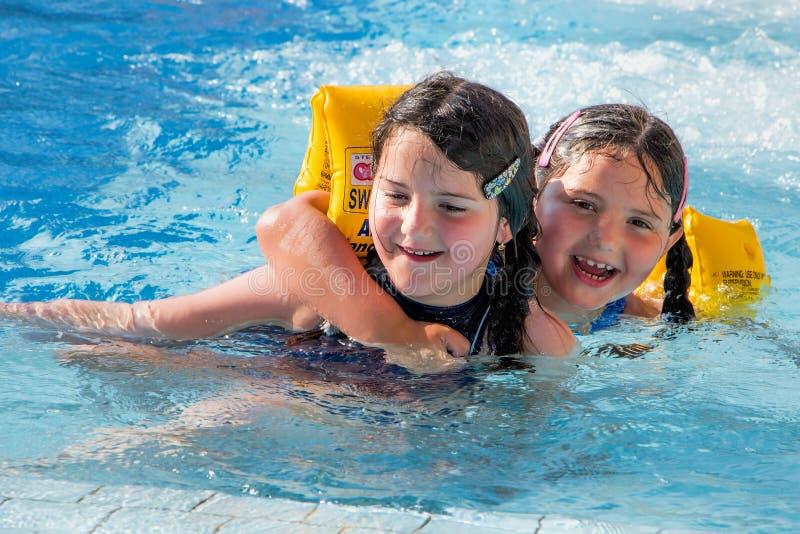 дети играя заплывание бассеина стоковое фото rf