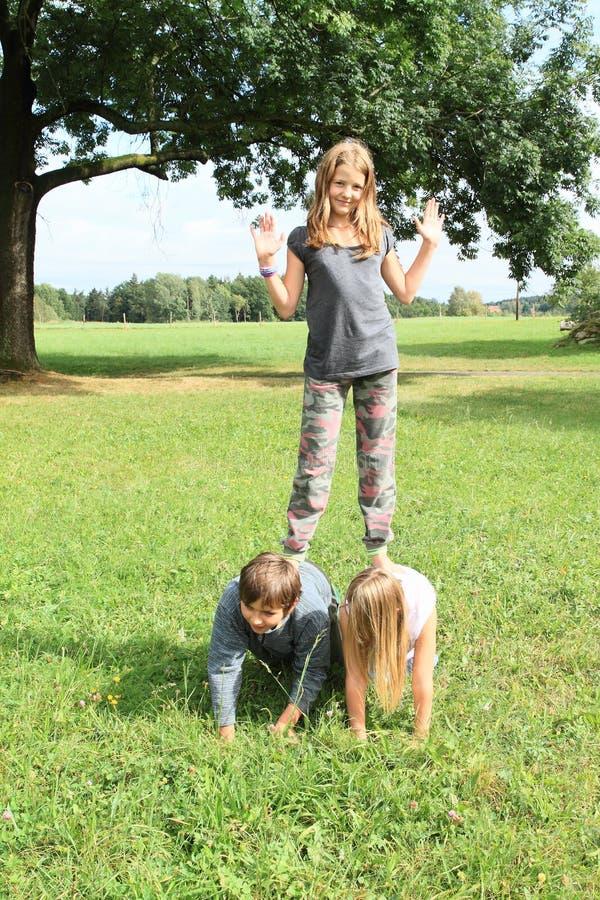 3 дет играя и стоя на одине другого стоковое фото