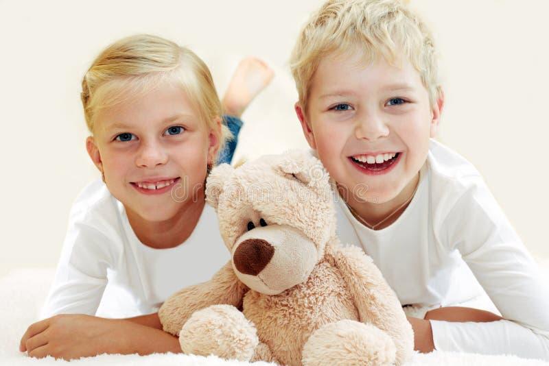 2 дет играя с плюшевым медвежонком стоковое изображение
