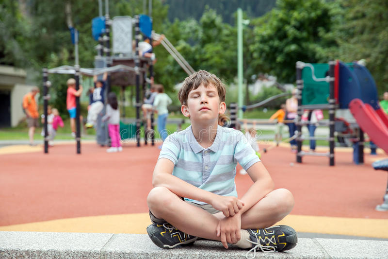 10 лет мальчика сидят на спортивной площадке cheldren стоковые фотографии rf