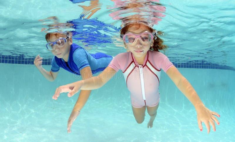 2 дет плавая под водой в бассейне стоковая фотография rf
