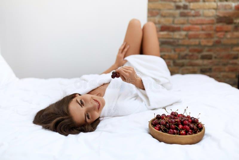 Еда здорового питания для здоровья женщины Девушка есть плодоовощи на кровати стоковые фотографии rf