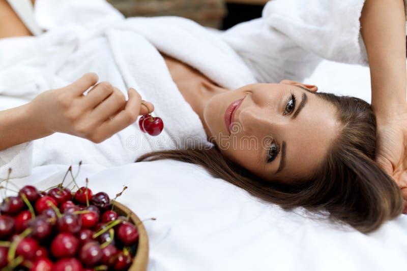 Еда здорового питания для здоровья женщины Девушка есть плодоовощи на кровати стоковая фотография rf
