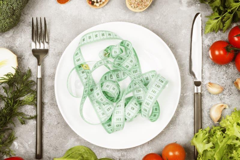 Еда концепции диетическая Белая плита и измеряя лента Различные овощи и специи брокколи, перец, томаты вишни, чеснок стоковое изображение