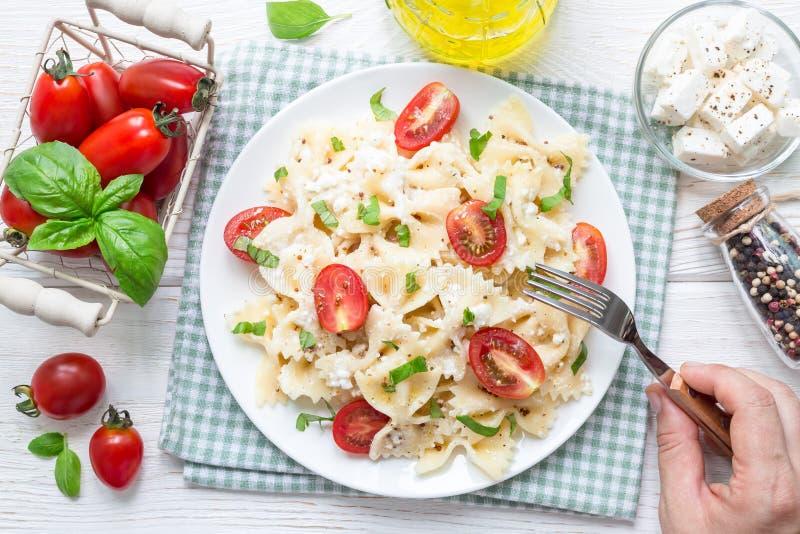 Еда салата макаронных изделий с макаронными изделиями связи, сыром фета, томатами, мустардом и базиликом, взгляд сверху, горизонт стоковое изображение