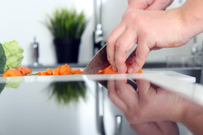 Еда, семья, варить и концепция людей - укомплектуйте личным составом прерывать морковь на разделочной доске с ножом в кухне стоковые изображения