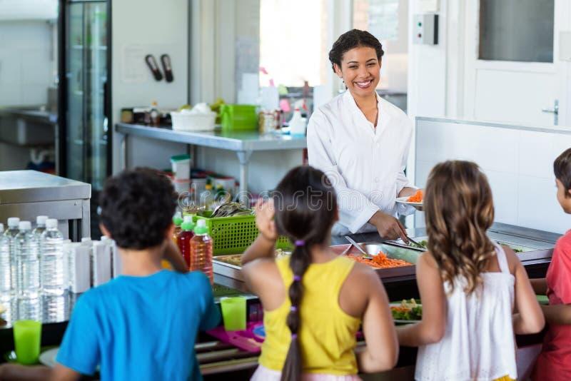 Еда сервировки женщины к школьникам стоковое фото