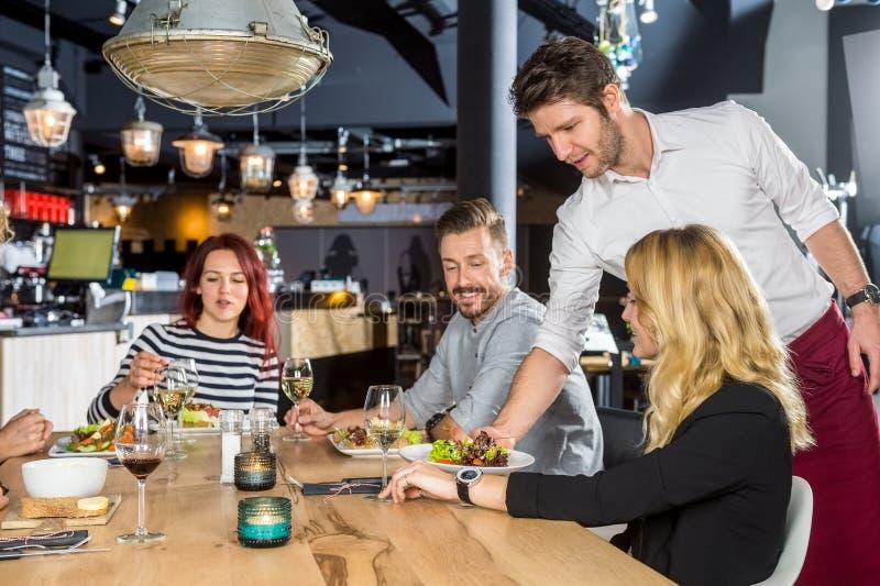 Еда сервировки кельнера к клиентам в кафе стоковая фотография