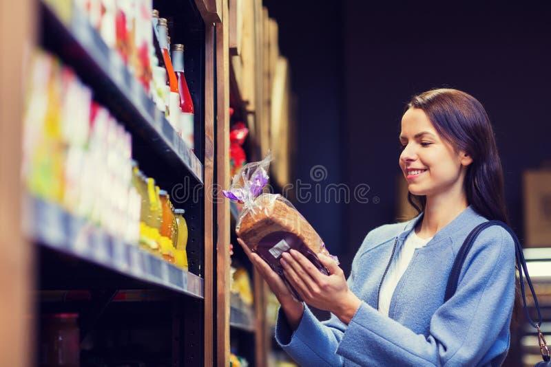 Еда счастливой женщины выбирая и покупая в рынке стоковая фотография rf