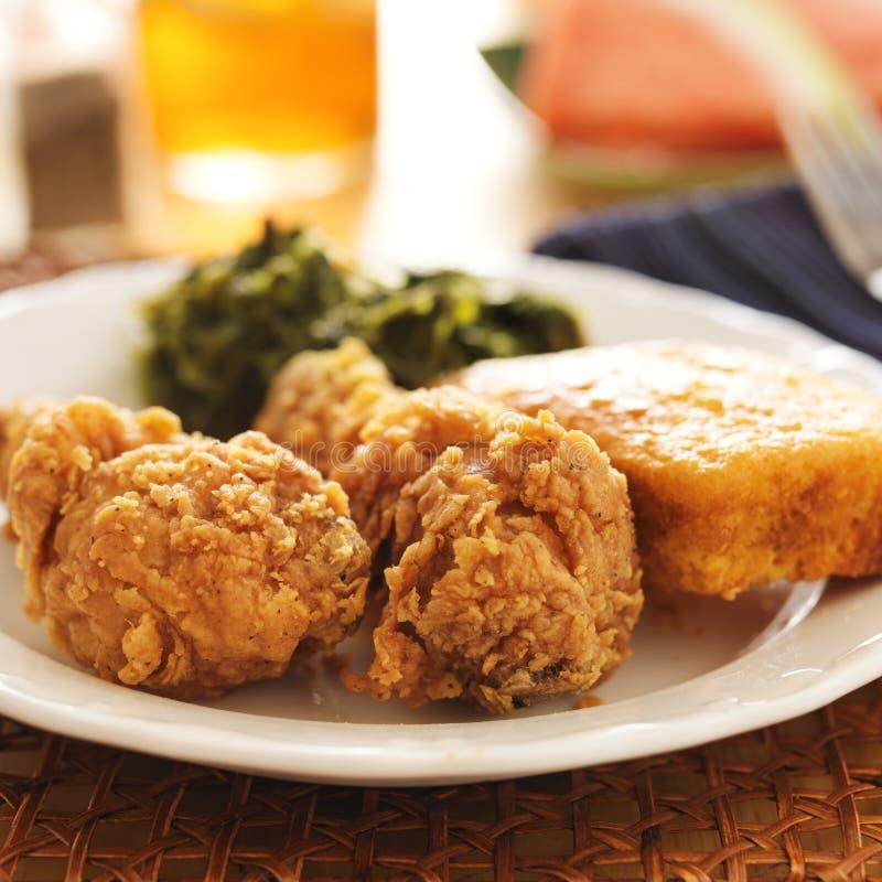 Еда души - жареная курица с зелеными цветами collard и хлебом мозоли стоковая фотография rf