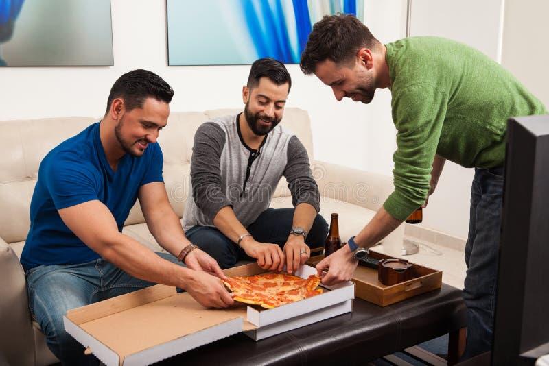 ел друзья собирают пиццу стоковые изображения rf