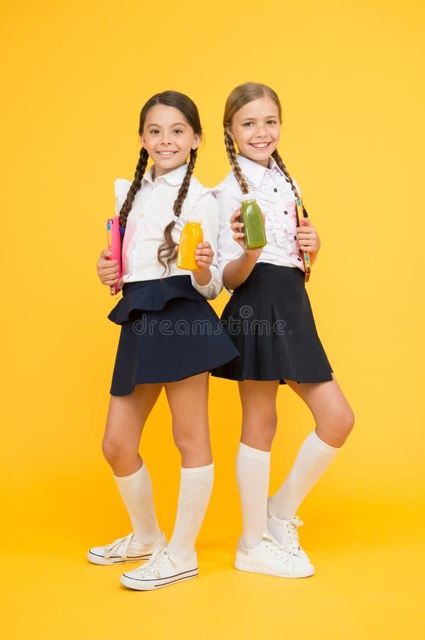 Жажда и обезвоживание m Школьницы держа бутылку сока на желтой предпосылке Гасить жажду стоковое изображение