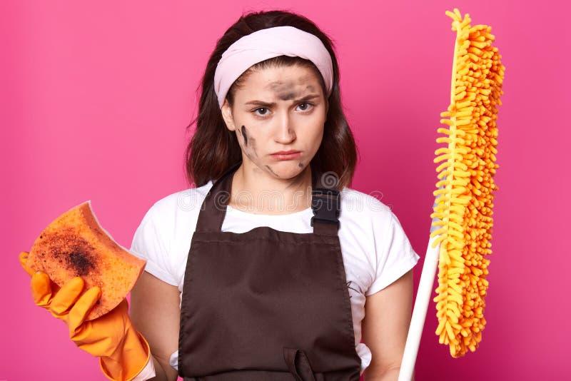 Жалкие расстроенные женские представления над розовой предпосылкой с mop и грязной ветошью в обеих руках, выглядят грустными, уто стоковое изображение rf