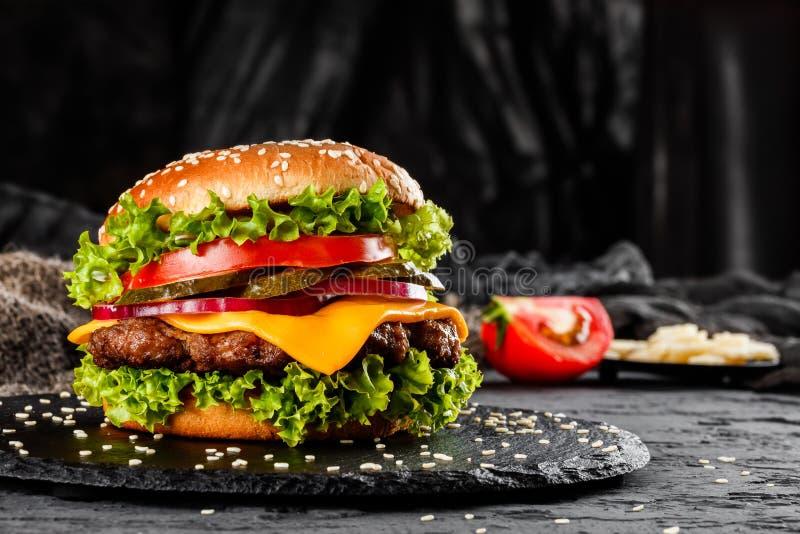 Жалуйтесь бургер с сыром, томатами, красными луками, огурцом и салатом на черном шифере над темной предпосылкой Нездоровая еда стоковое изображение rf