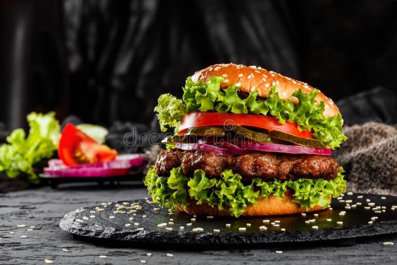 Жалуйтесь бургер с томатами, красными луками, огурцом и салатом на черном шифере над темной предпосылкой еда нездоровая стоковые изображения